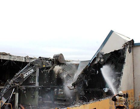 Worker spraying a building with water as it is demolished.